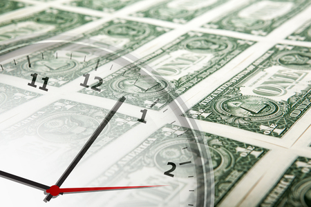 solvency: clock on the background of banknotes dollars close up Stock Photo