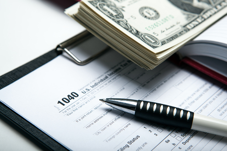 creditworthiness: dollars and tax return work close up