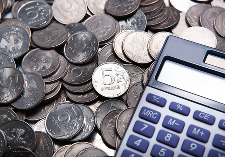 budget crisis: money in the form of coins with calculator close up