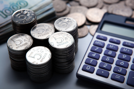budget crisis: money in the form of banknotes and coins with calculator close up