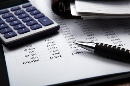 電卓・会計書類の背景にペン 写真素材