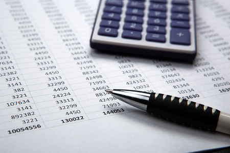emolument: pen on background of calculator and accounting papers