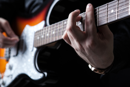 virtuoso: guitarist playing guitar on a black background Stock Photo