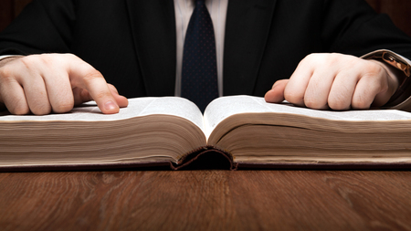 glossary: man is looking for information in the dictionary close up Stock Photo
