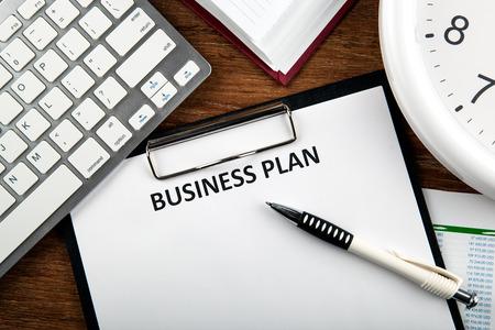Document met titel business plan en kantoorbenodigdheden en klok