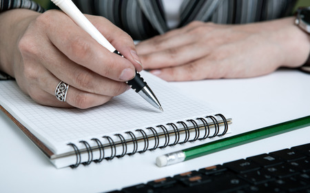authorship: diary and human hand holding a pen close-up Stock Photo