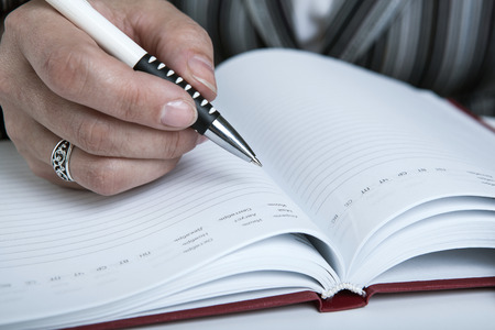 diary and human hand holding a pen close-up Stock Photo