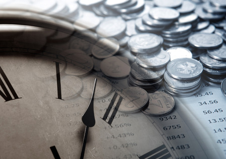 emolument: pile of coins with digits and clock face close up