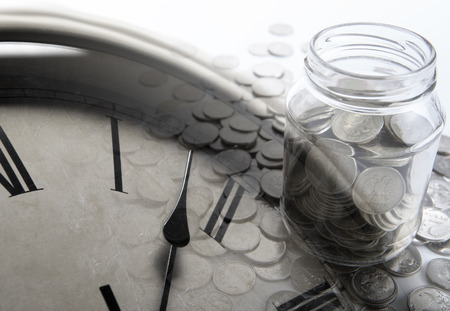 emolument: bank of coins with digits and clock face close up