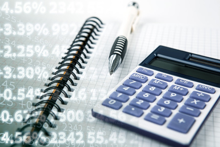 pen on a notebook and calculator and digits close up Stock Photo