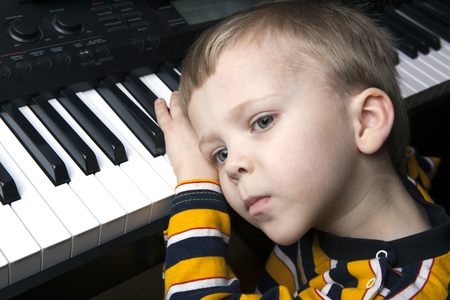 portrait of a dreaming little boy sitting at the piano Stock Photo