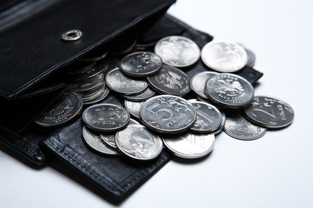 emolument: pocket purse with ruble coins on a white surface close up