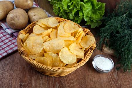 감자 칩과 생 감자와 초록색 유리 그릇