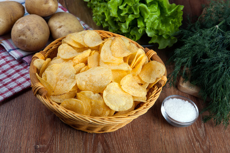 glass bowl with potato chips and raw potatoes and greenery