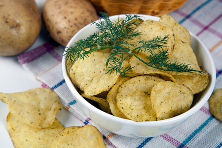 still life from a glass bowl with potato chips close up