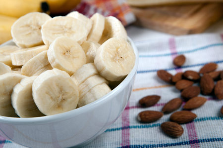 dulcet: Slices of fresh bananas in a bowl and nuts close up