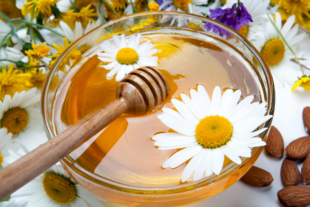 dulcet: fresh honey in a bowl and honey stick and flowers Stock Photo