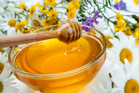 fresh honey in the bowl and honey stick and flowers