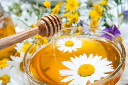 dulcet: fresh honey in the bowl and honey stick and flowers