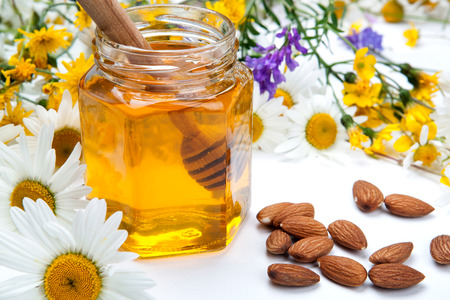 fresh honey in a bank and honey stick and flowers