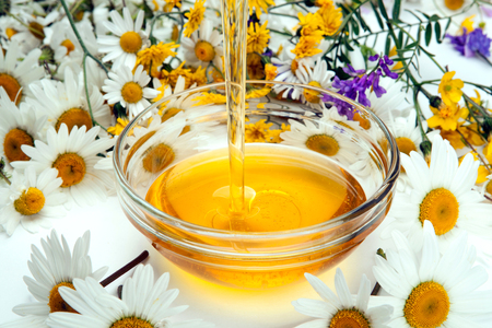 dulcet: fresh honey flows into a bowl and flowers Stock Photo