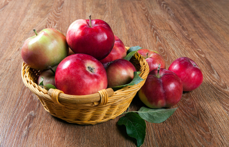 Still life of many apples on a napkin in the basket on a wooden table