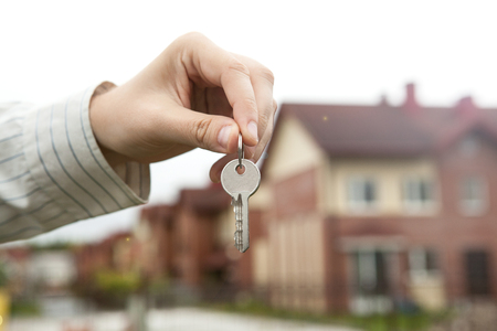 A mans hand holds the keys on the background of new buildings Stock Photo
