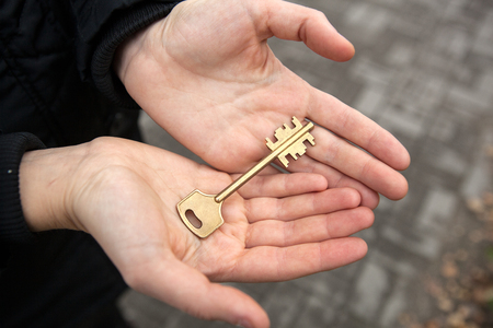 a female hand holds the key to an apartment in a new building