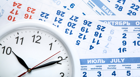 clock with wall calendar sheets with the number of days close up