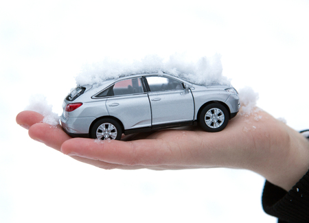 girl holds in her hand model of car with snow closeup