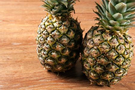Two pineapples on a wooden background closeup Фото со стока