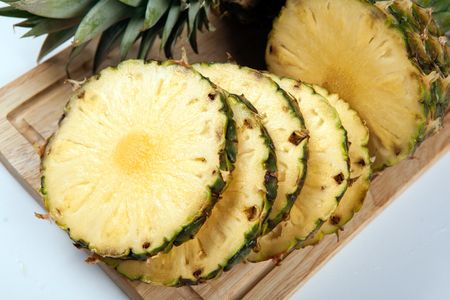 Round slices of pineapples on a cutting board closeup