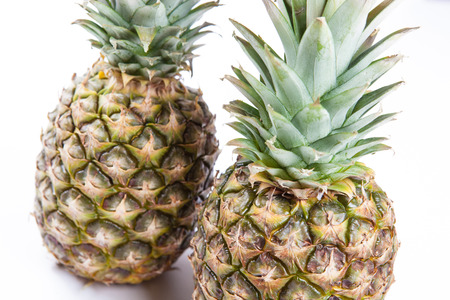 two big pineapples on a white background closeup