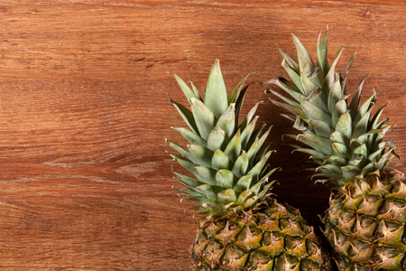 Two pineapples on a wooden background Stock Photo