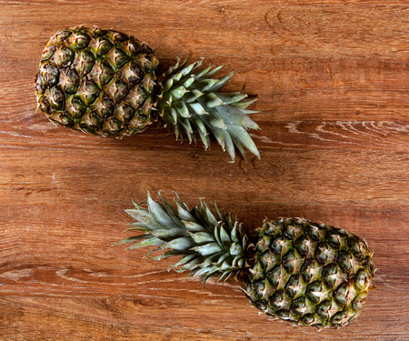 Two pineapples on a wooden background view from above