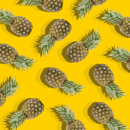 illustration in the form of yellow background with image of ripe pineapples Фото со стока
