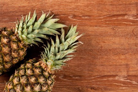 Two pineapples on a wooden background Фото со стока