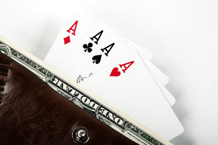 Four cards with aces and a dollar bill in a purse closeup