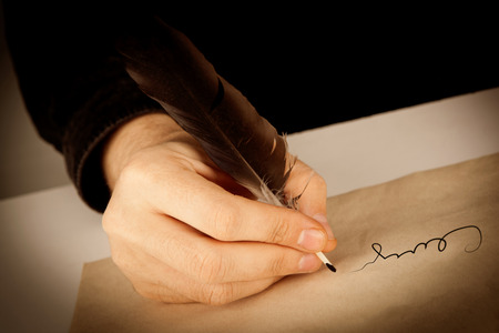 writer holds a fountain pen over writing paper and a signature closeup