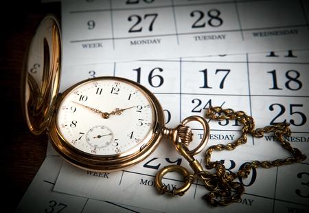 An antique gold pocket watch lies on calendar sheets