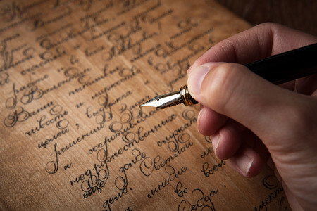 fountain pen in the hand on letter with text close up