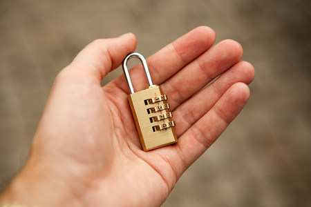 golden padlock with code in mans hand close up