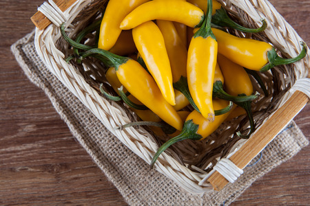 fruits of yellow fresh chilli pepper in the basket on a wooden background top view