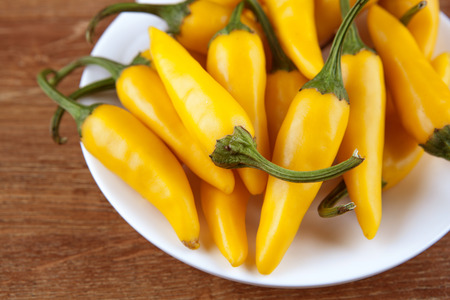 fruits of yellow fresh chilli pepper in a white plate close up Stock Photo