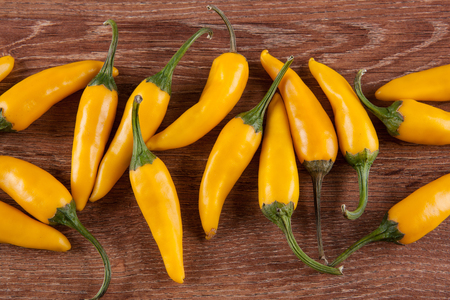 fruits of yellow fresh chilli pepper on a wooden background still life top view
