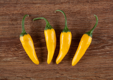 four fruits of yellow fresh chilli pepper on a wooden background still life top view