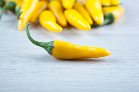 the one fruit of yellow fresh chilli pepper against the rest of the peppers close up Stock Photo