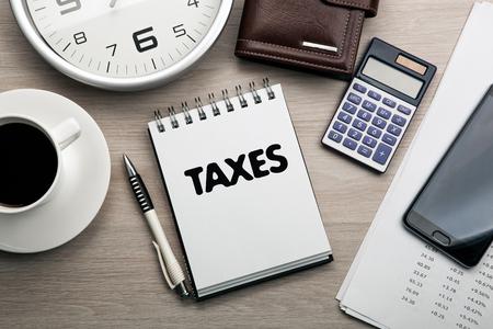 Geschäftsstillleben von einem Notizblock mit dem Text Steuern, einem Smartphone, einer Uhr, einer Tasse Kaffee, einem Taschenrechner