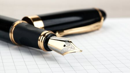 golden fountain pen on the notepad on a table closeup