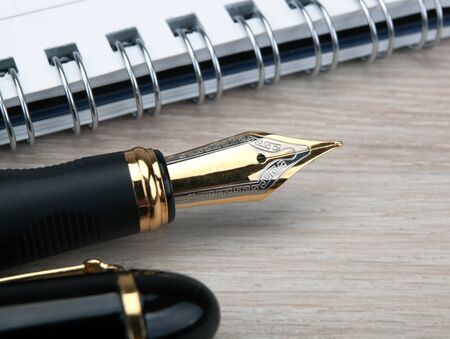 fountain pen near the notepad on a wooden table  closeup Stockfoto